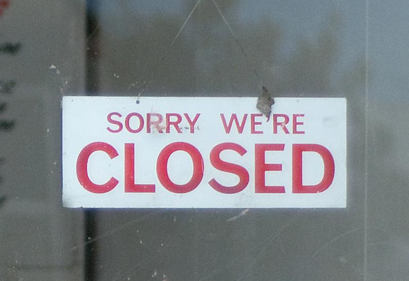 A closed sign hangs on a shop door obstr