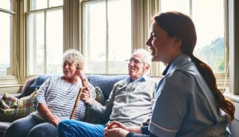 Smiling nurse visiting senior people at home