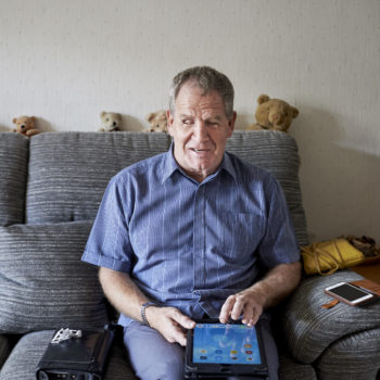 Visually impaired man using apps on a tablet device at home