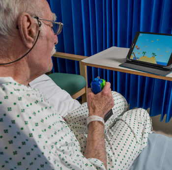 A patient and nurse at Charing Cross Hospital enjoy playing the game 'Gripable', designed by Imperial College researhcers, to help the patient overcome some of the after effects of his stroke, 13th November 2017Photography by Fergus BurnettAccreditati